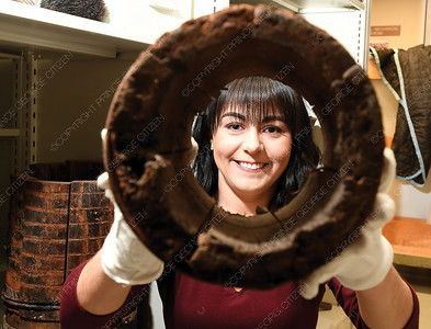 Exploration Place curator Alyssa Tobin looks through a section of the wooden water pipe that crews changed beside City Hall last fall. The city has donated chunks of the pipe as a reminder of the municipal water lines were built. Citizen photo by Brent Braaten