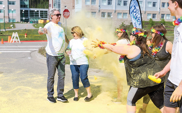 Mayor Lyn Hall, left, and MLA Shirley Bond get covered with a cloud of yellow colour on Sunday morning during the first annual Prince George Hospice Society Colour Walk at UNBC. Citizen Photo by James Doyle   May 26, 2019