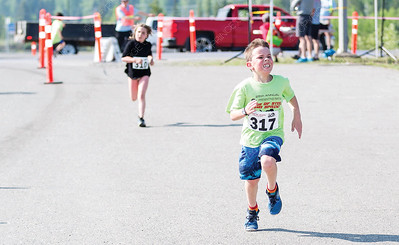 Eli Bernard gives it their all while crossing the finish line on Sunday morning while competing in the 25th Annual Integris Kids of Steel Triathlon. Citizen Photo by James Doyle      May 26, 2019