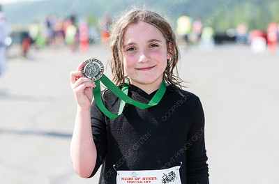 Peyten Barr poses with a medal on Sunday morning after competing in the 25th Annual Integris Kids of Steel Triathlon. Citizen Photo by James Doyle      May 26, 2019