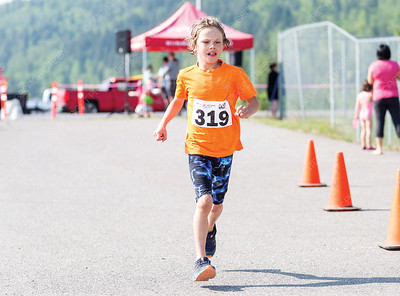 Sully Nelson crosses the finish line on Sunday morning while competing in the 25th Annual Integris Kids of Steel Triathlon. Citizen Photo by James Doyle      May 26, 2019