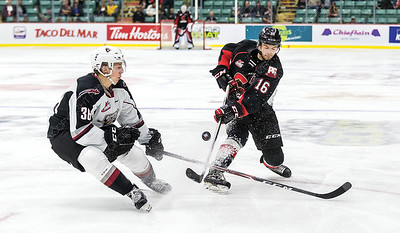 Prince George Cougars defender Ryan Schoettler tries to put a shot on goal past Vancouver Giants defender Justin Lies on Friday night at CN Centre during the Cougars home opener. Citizen Photo by James Doyle