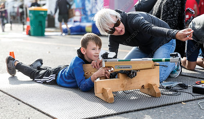 Stacey Sinclair, a volunteer parent with the Caledonia Nordic Ski Club, shows Davyn Hogan, 7, how to aim the biathon laser rifle at the CrossRoads Powersports, Skiing and Snowboarding Festival on Saturday morning. Citizen Photo by James Doyle