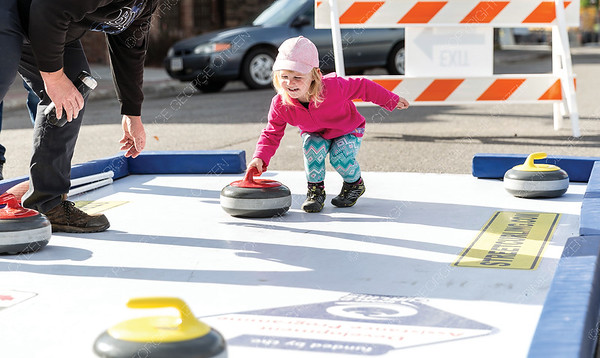 Amy Kranebusch, 3, tries out the outdoor curling rink at the CrossRoads Powersports, Skiing and Snowboarding Festival on Saturday morning. Citizen Photo by James Doyle