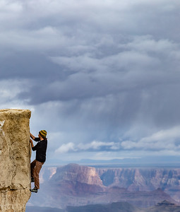 DA029,DJ,Rock climber scales sheer cliff face to summit rim of Grand Canyon