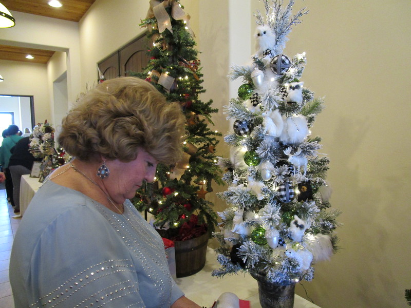 "Barbara Hartloff puts some tickets in for the ""Forest Critters"" tree as it matched her table which she decorated with white owls. The tree was designed by Maura Button. Lucette Moramarco photos"