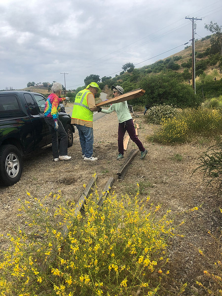 Volunteers work to clean up the Military Memorial site in Fallbrook including, from left, Jackie Heyneman; Dan Clouse, the steward of the Welcome Home Tribute, and Marta Donovan.