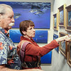 Greg Reuvers and his wife Sharon view paintings by artist Gamini Ratnavira on display during the Reflections of Nature art show reception.