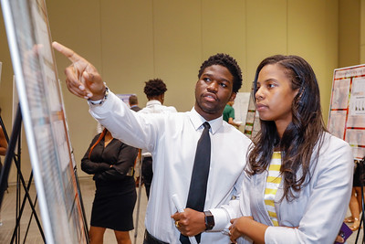 Dr.  Jaqueline Smith talks with Jason Dennis during Charles Herbert Flowers High School's science and technology program's research symposium, Wednesday, May 1, 2019.