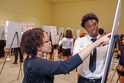 Dr. Tyesha Burks talks with student David Daramola during Charles Herbert Flowers High School's science and technology program's research symposium, Wednesday, May 1, 2019.