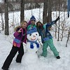 Mia, Peyton and Ellie build a snowman in front of our rental cabin at Powderhorn