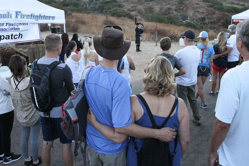 Hill climb participants gather to listen to a bagpiper perform during the opening ceremony of the ninth annual 9/11 Memorial Hill Climb at Monserate Mountain, Sept. 7.
