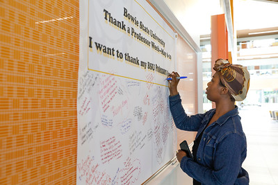 Whitney Okoe, a senior biology major, writes a message thanking her professors on a banner in the Center for Natural Sciences, Nursing and Mathematics, Tuesday, May 7, 2019.
