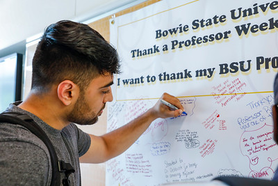 Rahmat Husain, junior biology major, writes a message thanking professors on a banner in the Center for Natural Sciences, Nursing and Mathematics, Tuesday, May 7, 2019.
