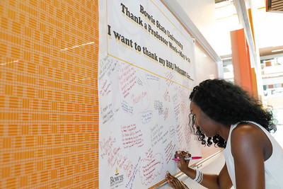 Simbiat Yusuf, a senior biology major, writes a message thanking her professors on a banner in the Center for Natural Sciences, Nursing and Mathematics, Tuesday, May 7, 2019.