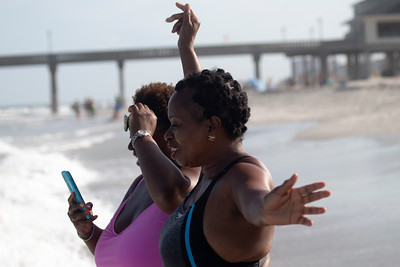 Foster mom Yolanda Blount-Wood, left, and Valerie Lingo cheer on Delilah Baker during Indo Jax Surf Charities 12th annual visually impaired surf camp that took place at Wrightsville Beach, N.C. Wednesday, July 17, 2019. The three-day camp involved more than 40 families and concludes on Thursday. The non-profit will hold a fundraiser this Saturday at Liberty Tavern from 1 p.m. – 6 p.m. for their surf therapy programs. [HALEY FRANCE/STARNEWS]