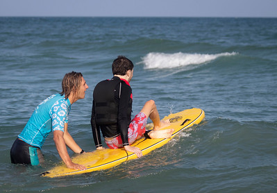 Walker Berry, right, is pushed into the water during Indo Jax Surf Charities 12th annual visually impaired surf camp that took place at Wrightsville Beach, N.C. Wednesday, July 17, 2019. The three-day camp involved more than 40 families and concludes on Thursday. The non-profit will hold a fundraiser this Saturday at Liberty Tavern from 1 p.m. – 6 p.m. for their surf therapy programs. [HALEY FRANCE/STARNEWS]