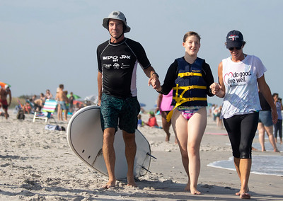Shaun Seufert, from left, Delilah Baker and Diane Kimrey walk along the beach during Indo Jax Surf Charities 12th annual visually impaired surf camp that took place at Wrightsville Beach, N.C. Wednesday, July 17, 2019. The three-day camp involved more than 40 families and concludes on Thursday. The non-profit will hold a fundraiser this Saturday at Liberty Tavern from 1 p.m. – 6 p.m. for their surf therapy programs. [HALEY FRANCE/STARNEWS]