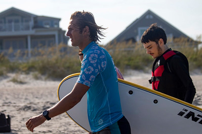 Walker Berry, right, follows a surf instructor to the water at Indo Jax Surf Charities 12th annual visually impaired surf camp that took place at Wrightsville Beach, N.C. Wednesday, July 17, 2019. The three-day camp involved more than 40 families and concludes on Thursday. The non-profit will hold a fundraiser this Saturday at Liberty Tavern from 1 p.m. – 6 p.m. for their surf therapy programs. [HALEY FRANCE/STARNEWS]