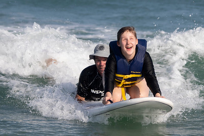 Surf instructor Shaun Seufert and Delilah Baker ride a wave during Indo Jax Surf Charities 12th annual visually impaired surf camp that took place at Wrightsville Beach, N.C. Wednesday, July 17, 2019. The three-day camp involved more than 40 families and concludes on Thursday. The non-profit will hold a fundraiser this Saturday at Liberty Tavern from 1 p.m. – 6 p.m. for their surf therapy programs. [HALEY FRANCE/STARNEWS]
