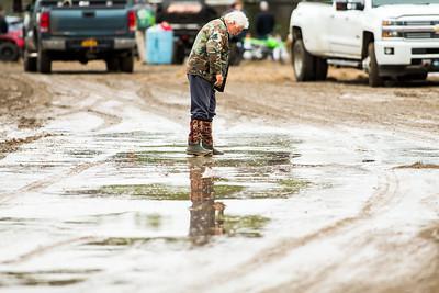 Race fan walking through a muddy pit area