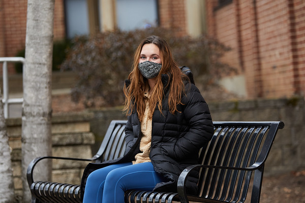 First year student Maddie Kozel sits in front of Coate Hall. Maddie wrote a first person perspective of life in Coate Hall during the COVID-19 Pandemic.