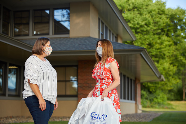 Left, Ruth Kinstler of RSVP hands Lisa Klein of UW-La Crosse a donation of homemade masks for students at the university during the COVID pandemic.