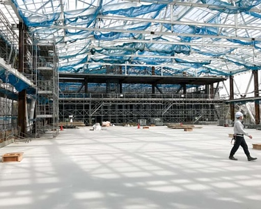 An interior view of the double gym's structural frame and roof beams in the South Building provides an impressive sense of scale. The section for spectator seating is visible at the far end on the second level.