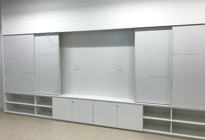 Classrooms will feature built-in storage cabinetry with a large LCD display mounted behind sliding whiteboards.