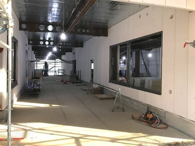 Covered open-air corridor in South Building; large window at right is future PE office.