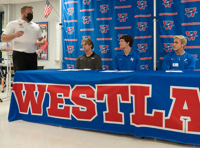 Chap Lacrosse Head Coach Zach Beard (L) congratulates Christian Fournier, Ollie Lovell (C) and Brooks Jeffers (R) for signing to play in college, during the college signing day at Westlake High School on April 14, 2021. [PAUL BRICK]