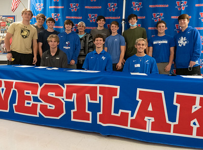 Christian Fournier, Ollie Lovell (C) and Brooks Jeffers (R) celebrate with their team mates after signing to play Lacrosse in college, during the college signing day at Westlake High School on April 14, 2021. [PAUL BRICK]