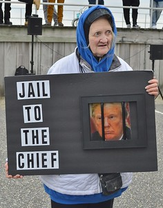 This woman at an anti-Trump protest holds a sign picturing Donald Trump behind bars. The President spoke later at the Wildwoods Convention Center (N.J.).