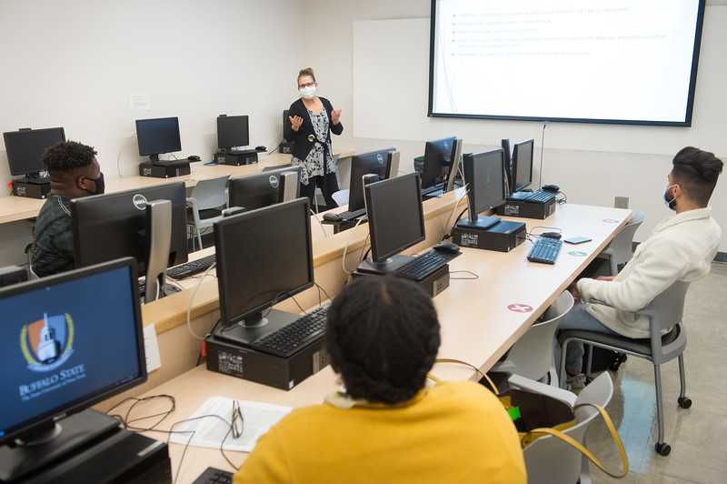 Professor Martha Skerrett meeting with graduate students in SAMC computer lab at SUNY Buffalo State College.