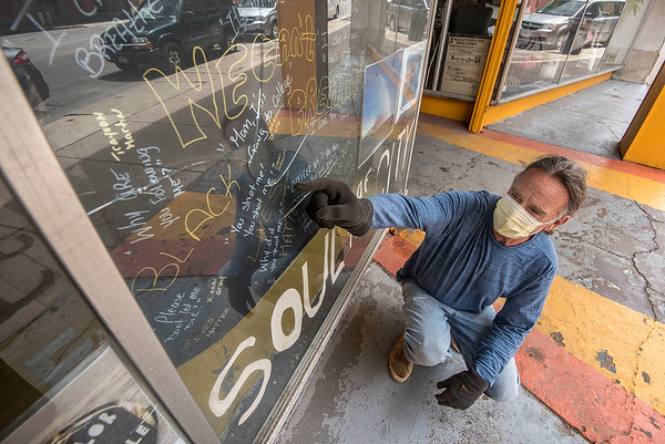 200624 Book Corner 1<br /> James Neiss/staff photographer <br /> Niagara Falls, NY - Book Corner owner Jeffrey Morrow points to a series of cracks in the window of his book store, behind which are signs protesters made for the peaceful rallys downtown. Customer Allison Congi noticed the cracks and posted them online. A friend of hers, Lynne Neveu saw the post and started a fundraising campaign online, raising $1530 in 4 hours. Morrow said if there is money left over after replacing the window, he is donating it in some form to local charity.