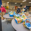 201221 NFHS Food Delivery<br /> James Neiss/staff photographer <br /> Niagara Falls - Niagara Falls Dean of Students Marc Catanzaro, left, grabs a bag for delivery to a needy family packed by school resource officers Kris Proietti, center, and Daniel Banas. After Wegmans donated 100 turkeys, the Niagara Falls High School teachers and staff raised $1000 to buy $25 Wegmans gift cards so recipients can buy the fixings for a holiday turkey dinner. At the end of the work day on Monday and Tuesday, staff members grabbed a bag to be delivered on their way home. <br /> <br /> From: SConstantino@nfschools.net<br /> Subject: Holiday Turkeys<br /> Date: December 15, 2020 at 5:51:51 PM EST<br /> To: mark.scheer@niagara-gazette.com<br /> <br /> Hi Mark, Next Monday and Tuesday starting at 2:30 til 4pm each  day NFHS staff will be delivering 100 turkeys to local families, the turkeys were donated  by Wegmans. I was wondering if that would be worth  a story or hopefully we could get a photographer to come by. You can respond to this email or call my cell 228-7916. Looking forward to hearing from you.