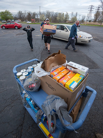200514 NT Food Drive 1<br /> James Neiss/staff photographer <br /> North Tonawanda, NY - County Legislator Rich Andres, one of many volunteers, carries a box of food dropped off at the Knights of Columbus Madona Council 2535 on Erie Avenue during a food drive to benefit the North Tonawanda Food Bank.