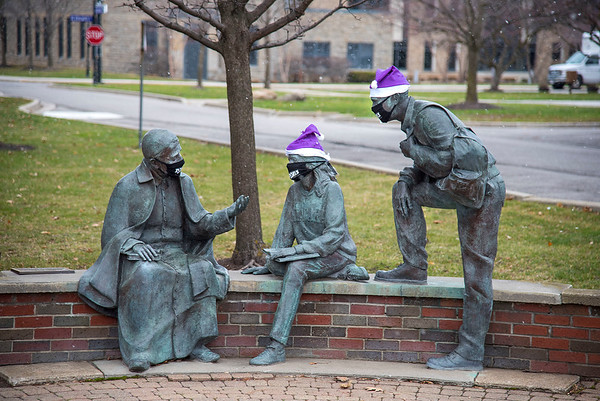 """201215 Enterprise<br /> James Neiss/staff photographer <br /> Lewiston, NY - Someone at Niagara University has a fun sense of humor decorating the """"St. Vincent and his Friends"""" statue with holiday hats and making sure they all wear their masks. St. Vincent de Paul, is the founder of the Vincentian Fathers and Brothers who sponsor Niagara University and dedicated his life to the service of the poor."""