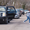 200411 Teachers Tribute 3<br /> James Neiss/staff photographer <br /> Niagara Falls, NY - A parade of bumper to bumper cars were backed up several blocks as NFHS 11th grader Michael Murgia places flowers at the curb for his former teachers home. Unable to gather for a funeral because of the COVID-19 Pandemic, a group of friends, colleagues and students honored Theatre Teacher Kate Muldoon's passing by singing songs in her front yard, as those in a parade of cars got out as they passed her James Avenue home to place flowers and cards.