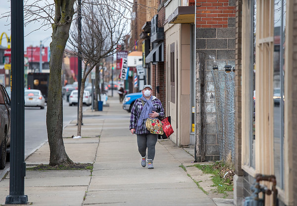 James Neiss/staff photographer <br /> Niagara Falls, NY - Kerri Bozek walks along Pine Avenue and like many Americans, now wears a mask while out in public.