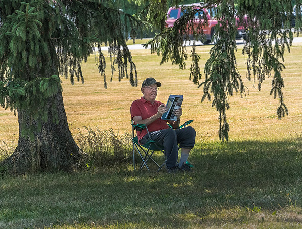200714 LKPT Enterprise 2<br /> James Neiss/staff photographer <br /> Lockport, NY - Richard Feltz of Davison Road found a nice shade tree across the street from his home to smoke a cigar and enjoy some light reading under a huge shade tree.