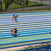 "200520 Enterprise A<br /> James Neiss/staff photographer <br /> Lewiston, NY - Laura Winslow, Zoe Zecher, Stephanie Kowalski and Tanis Winslow, director of visual and family programs, touch up the parking lot painting titled ""Niagara 1979,"" by artist Gene Davis at Artpark."
