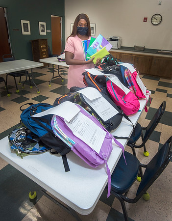 200828 Backpack Giveaway<br /> James Neiss/staff photographer <br /> Niagara Falls, NY - Marthe Limage, resource development coordinator at Heart, Love & Soul shows off some of the approximate 40 backpacks filled with school supplies being given away to local school children that signed up for the back to school giveaway.