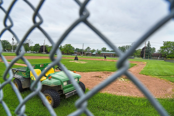 200602 Lockport Enterprise<br /> James Neiss/staff photographer <br /> Lockport, NY - Volunteers Jeff Ziemecki and Ryan Wayne work on Lockport Little Leagues Field A on Lincoln Ave. in hopes that kids will again hit the field this summer.