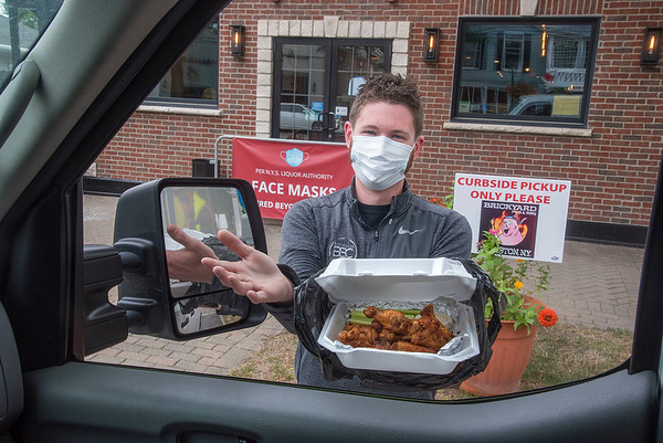 200911 Brickyard 1<br /> James Neiss/staff photographer <br /> Lewiston, NY - Brickyard front end manager Paul Beatty shows off an order of smoked chicken wings he's delivering to a customer at curbside pickup. The popular restaurant is undergoing reconstruction after a fire, but is open for curbside pickup 4 p.m. - 9 p.m. Monday thru Thursday and from 11 a.m. Friday thru Sunday.