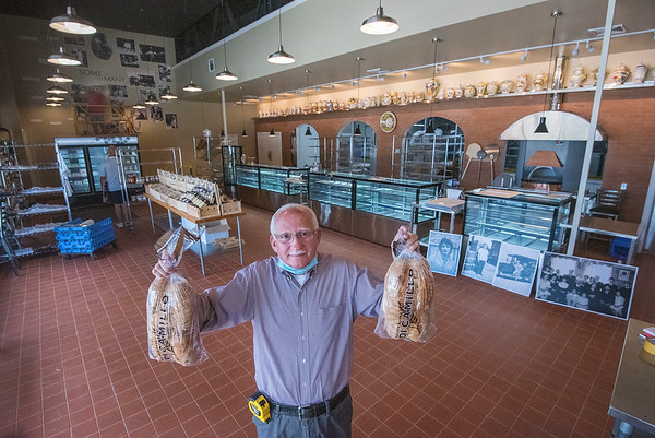 200728 DiCamillo 2<br /> James Neiss/staff photographer <br /> Niagara Falls, NY - Skip DiCamillo holds up two loaves of Niagara Falls favorite bread as finishing touches are being made at the newly redesigned DiCamillo Bakery store.