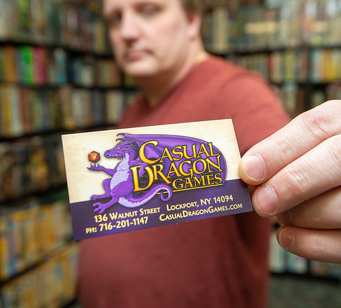 200915 LKPT Artist 3<br /> James Neiss/staff photographer <br /> Lockport, NY - Casual Dragon Games owner shows off the artwork of Jeremy Sniatecki that's being used on game boxes, card game cards and store branding.