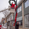 201118 Enterprise 3 A<br /> James Neiss/staff photographer <br /> Lockport, NY - Lockport Highway Department crewmen Dan Cole hangs the wreath as Tom Furlong  wraps the pole with garland as the crew install Christmas decorations all along Main Street.