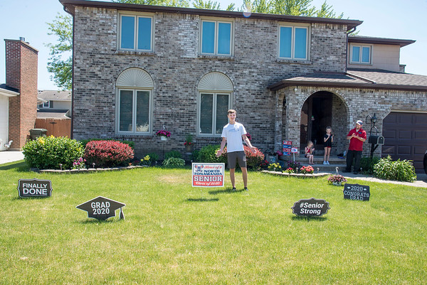 2006017 NT Seniors 1<br /> James Neiss/staff photographer <br /> North Tonawanda, NY - North Tonawanda Class of 2020 graduate Ethan Busse, 17, stands among the festive signage in his front yard in lieu of an actual graduation ceremony because of the COVID-19 pandemic. Family members Charlotte Duffy, 5, Emma Duffy 8 and stepfather Ryan Duffy give applause. Ethan will be attending NCCC in the fall, he said.