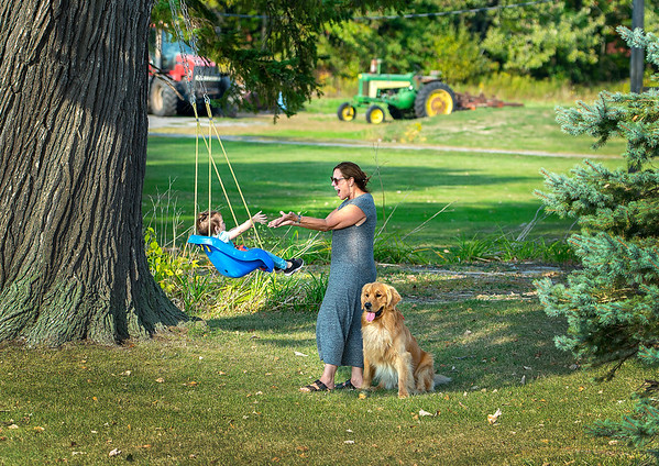 """200924 Wilson PP 1<br /> James Neiss/staff photographer <br /> Wilson, NY -  Afternoon in the Country - """"Grammy,"""" Lynne Moley, and her 19 month old granddaughter have a swinging good time in her Wilson front yard. The two were joined by Hank the dog who was patiently waiting to play fetch."""